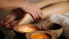 A jovem mulher obtém uma massagem do pé no salão de beleza dos termas Close-up das velas corrediça masculina das mãos nos pés fêm video estoque