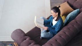 Jovem mulher ocasional de sorriso do ângulo alto que lê entusiasticamente a página de gerencio do livro filme