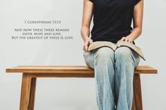 A jovem mulher ocasional guarda um 13:13 aberto dos corinthians da Bíblia 1 sobre ele Imagem de Stock