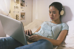 Jovem mulher ocasional que encontra-se na cama e que usa o portátil em casa Imagem de Stock