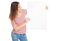 Jovem mulher ocasional que guardara uma placa branca Foto de Stock