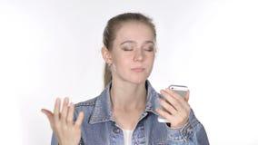 Jovem mulher ocasional que reage ao quando da perda usando Smartphone video estoque
