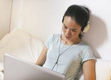 Jovem mulher ocasional que senta-se na cama e que usa o portátil em casa Fotos de Stock