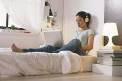 Jovem mulher ocasional que senta-se na cama e que usa o portátil em casa Fotografia de Stock Royalty Free