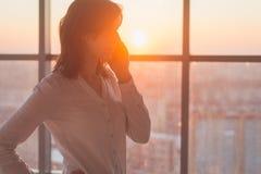 Jovem mulher ocupada com chamada, conversando no retrato da opinião lateral do telefone celular Imagem do close-up de uma mulher  imagem de stock