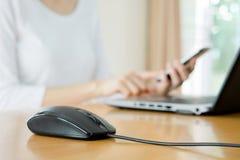 A jovem mulher ocupada está datilografando no laptop e está usando p móvel imagem de stock