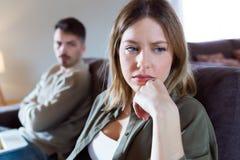 Jovem mulher ofendida que ignora seu sócio irritado que senta-se atrás dela no sofá em casa fotografia de stock