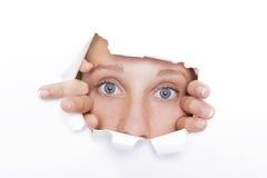 A jovem mulher olha através de um furo Fotografia de Stock Royalty Free