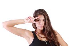 A jovem mulher olha através do sinal da paz Imagem de Stock Royalty Free