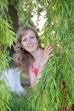 A jovem mulher olha devido aos ramos do salgueiro Fotografia de Stock