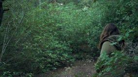 A jovem mulher olha a natureza em torno dela filme