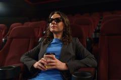 A jovem mulher olha o filme 3D no cinema e bebe o café, lo Imagem de Stock Royalty Free