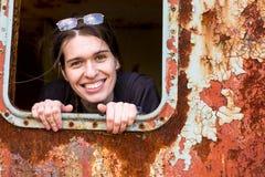 A jovem mulher olha para fora a janela de um carro de trem oxidado Fotografia de Stock