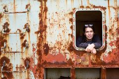 A jovem mulher olha para fora a janela de um carro de trem oxidado Imagens de Stock Royalty Free