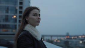 A jovem mulher olha para a frente a nivelar o scape da cidade filme
