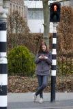 A jovem mulher olha seu telefone celular e não paga a atenção a fotografia de stock royalty free