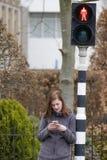 A jovem mulher olha seu telefone celular e não paga a atenção a imagens de stock royalty free