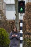 A jovem mulher olha seu telefone celular e não paga a atenção a imagens de stock