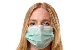 Jovem mulher olhando de sobrancelhas franzidas que veste uma máscara protetora fotos de stock