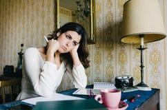 Jovem mulher oprimida que trabalha em casa imagem de stock
