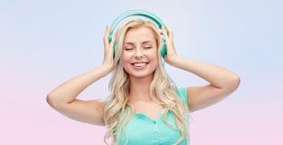 Jovem mulher ou adolescente feliz com fones de ouvido Foto de Stock Royalty Free