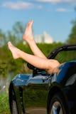 Jovem mulher ou seus pés em um cabriolet Fotos de Stock