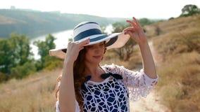 A jovem mulher pôs sobre o chapéu video estoque
