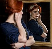 A jovem mulher põe sobre brincos bonitos na frente do espelho Menina bonita no estilo do vintage imagens de stock royalty free