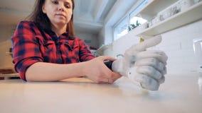 A jovem mulher põe sobre uma prótese biônico da mão, fim acima