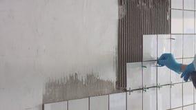 A jovem mulher p?s um azulejo sobre a parede vídeos de arquivo