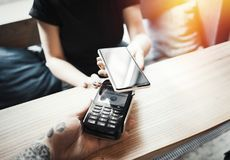 A jovem mulher paga através do terminal e do telefone celular do pagamento fotos de stock