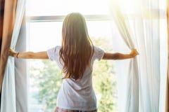Jovem mulher para acordar e abrir as cortinas na manh? para obter o ar fresco e a luz do sol fotografia de stock royalty free