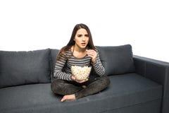 A jovem mulher passa seu tempo livre que olha a tevê no sofá que masca microplaquetas e fundo do branco da pipoca Foto de Stock