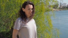 Jovem mulher pelo rio Menina na água com cabelo tornando-se Um dia ensolarado da mola filme
