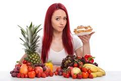 A jovem mulher pensa sobre comer um bolo um pouco do que frutos ou vegetais Fotografia de Stock
