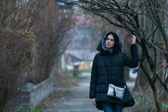A jovem mulher pensativa, morena, em um lenço, está andando no cit velho foto de stock