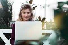 Jovem mulher pensativa nos vidros usando um computador, sentando-se em um banco em um parque da cidade O conceito do tempo est? e imagem de stock royalty free