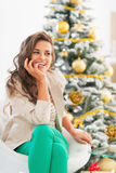 Jovem mulher pensativa que senta-se na frente da árvore de Natal Imagens de Stock Royalty Free