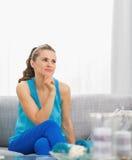 Jovem mulher pensativa que senta-se na sala de visitas Imagem de Stock