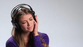 Jovem mulher pensativa triste bonita nos fones de ouvido vídeos de arquivo