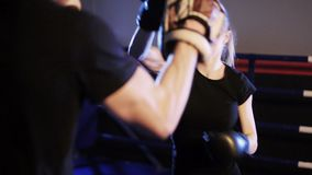 A jovem mulher perfura as luvas do foco no gym do encaixotamento filme
