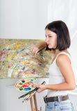 A jovem mulher pinta uma imagem Fotos de Stock