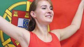 A jovem mulher portuguesa comemora guardar a bandeira de Portugal no movimento lento vídeos de arquivo