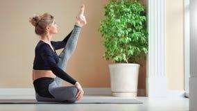 Jovem mulher positiva atrativa da flexibilidade que mostra o assento de esticão perfeito na esteira filme