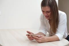 Jovem mulher positiva bonita com smartphone imagem de stock royalty free