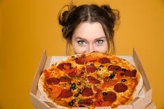 Jovem mulher positiva bonito bonita que esconde atrás da pizza Imagens de Stock