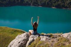 Jovem mulher positiva que aprecia a liberdade na parte superior da montanha com o ritom do lago como o fundo imagens de stock