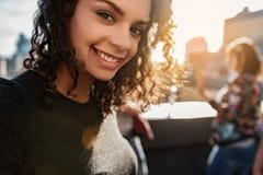 Jovem mulher positiva que fotografa-se no terraço do telhado Foto de Stock Royalty Free