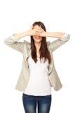 A jovem mulher próxima seu ` s eyes com mãos Imagens de Stock Royalty Free
