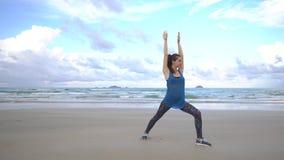 A jovem mulher pratica a ioga em uma praia no nascer do sol na frente do mar Manhã ginástica Mãos da elevação vídeos de arquivo
